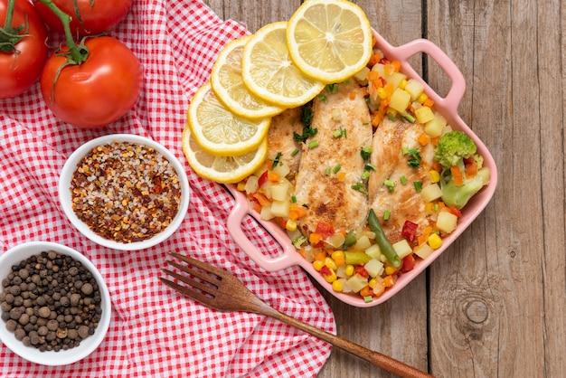 Frango caseiro assado no forno com legumes e limão. talheres. vista do topo.