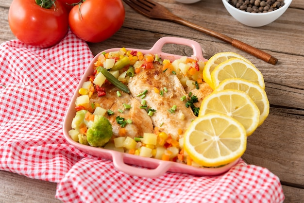 Frango caseiro assado no forno com legumes e vista de cima de limão