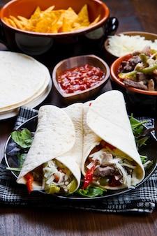 Frango caseiro e fajitas de carne com legumes e tortilhas