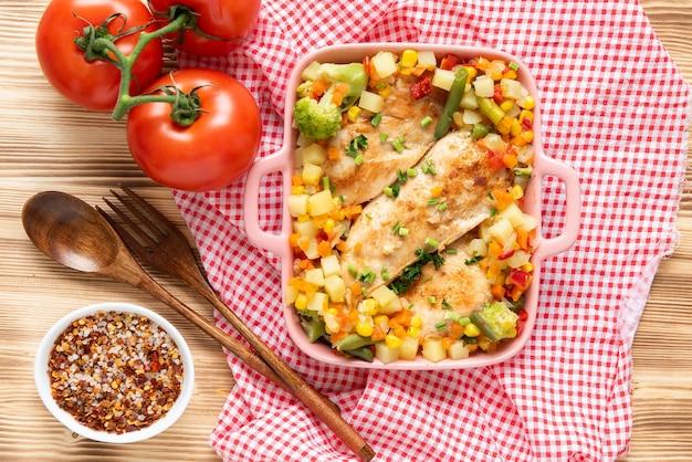 Frango caseiro grelhado com vários vegetais deliciosos em um fundo claro de madeira