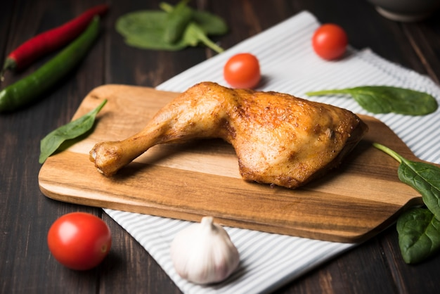 Frango close-up na placa de madeira com ingredientes