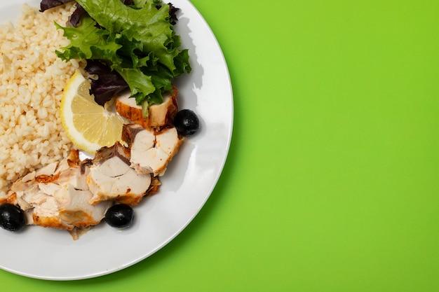 Frango com arroz cozido e salada em prato branco