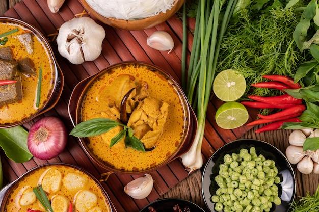 Frango com curry vermelho em uma tigela com pimentões secos, manjericão, pepino e feijão longo