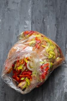 Frango com ervas, pimenta vermelha, cebola em saco plástico para cozinhar