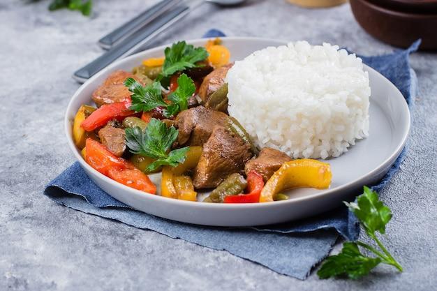 Frango com legumes com arroz no prato no fundo da mesa de pedra cinza. comida tailandesa azia