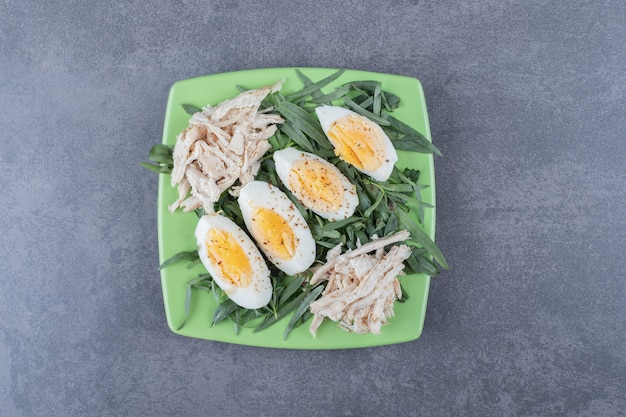 Frango com ovos cozidos na placa verde.