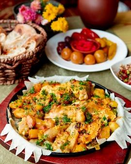 Frango cozido com batatas e servido com verduras