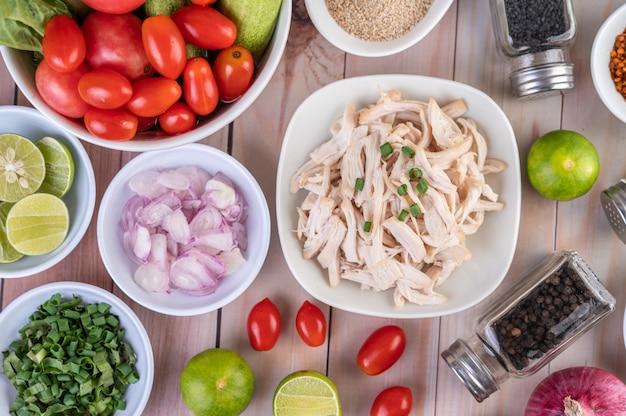 Frango cozido cortado em pedaços em um prato branco sobre uma mesa de madeira.