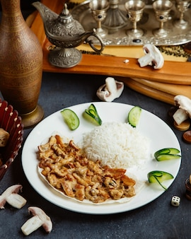 Frango cremoso e cogumelos fritos, servido com arroz, guarnecido com pepino