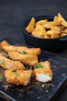 Frango crocante e batatas na mesa escura