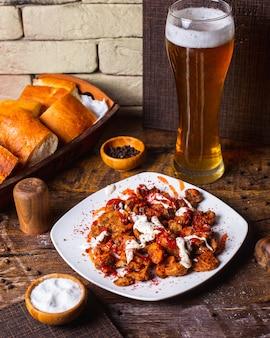 Frango crocante frito servido com molho e cerveja