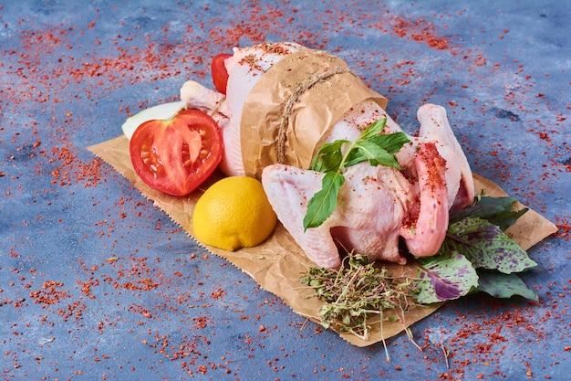Frango cru com legumes em uma placa de madeira em azul