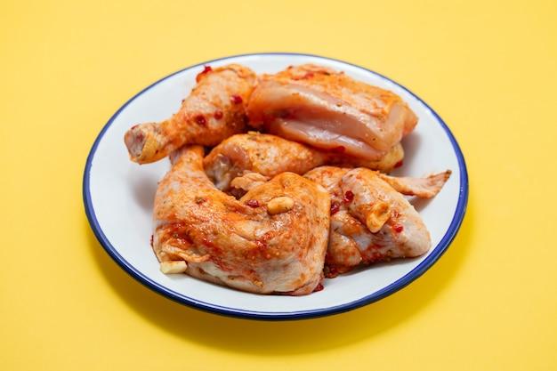 Frango cru com molho no prato branco sobre fundo amarelo