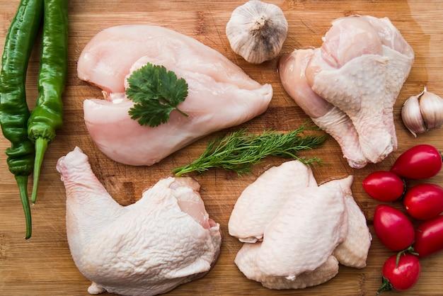 Frango cru e ingredientes para cozinhar na mesa de madeira