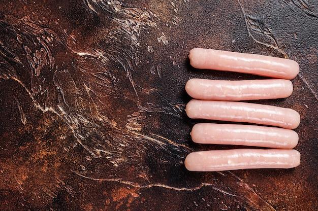 Frango cru e salsichas de carne de peru na mesa do açougueiro