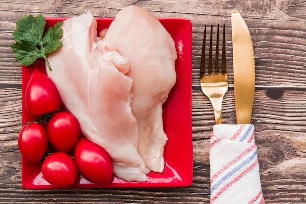 Frango cru e tomates no prato com garfo e faca
