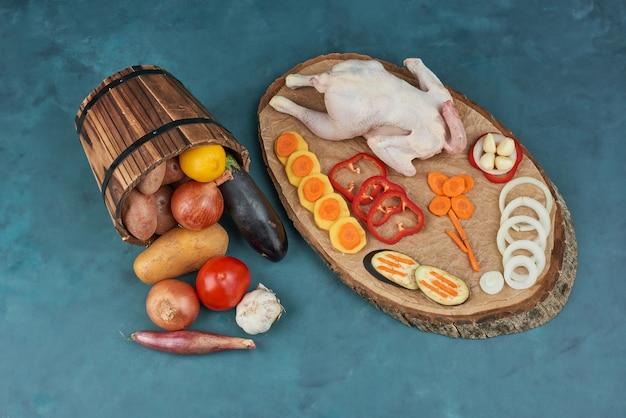 Frango cru em uma placa de madeira com ervas e vegetais no balde.