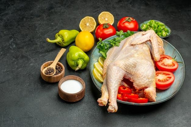 Frango cru fresco de vista frontal dentro do prato com verduras, limão e vegetais em fundo escuro.