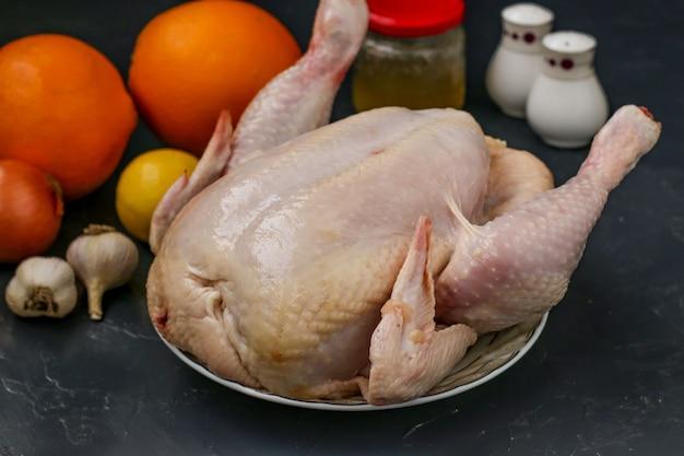 Frango cru prepara-se para assar no forno com mel, laranjas, limões e alho, fundo escuro, orientação horizontal