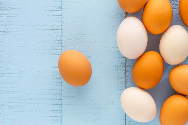 Frango e pato ovos na mesa de madeira.