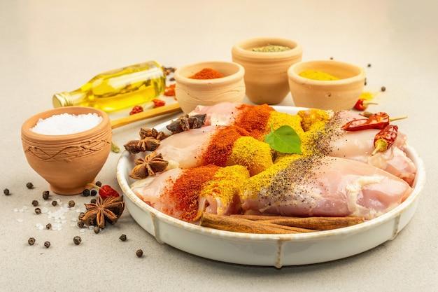 Frango e temperos com caril. conjunto de ingredientes crus para cozinhar alimentos tradicionais. fundo de concreto de pedra clara, close-up