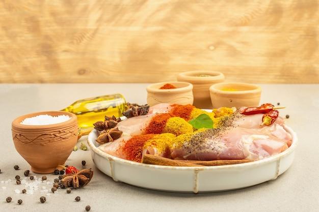 Frango e temperos com caril. conjunto de ingredientes crus para cozinhar alimentos tradicionais. fundo de concreto de pedra clara, copie o espaço
