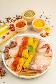 Frango e temperos com caril. conjunto de ingredientes crus para cozinhar alimentos tradicionais. fundo de concreto de pedra clara, vista superior