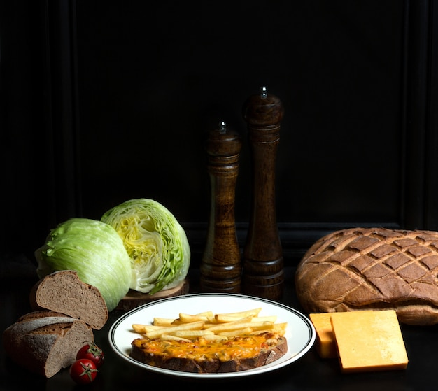 Frango e tomate coberto com queijo ralado no pão e batata frita