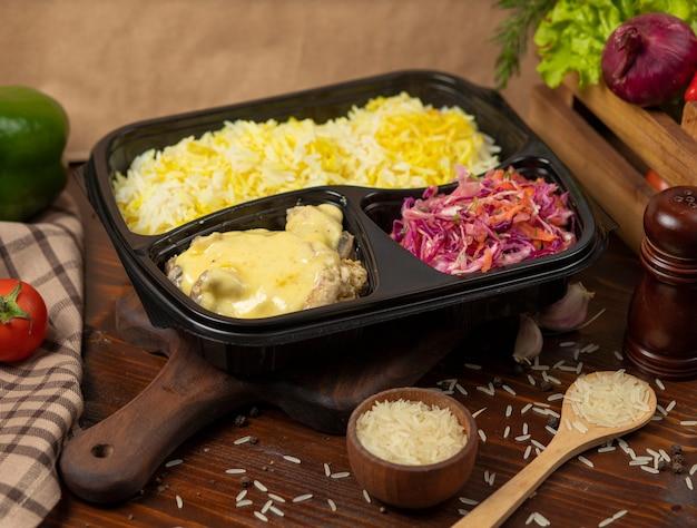 Frango em molho de queijo creme derretido com guarnição de arroz e salada de cenoura repolho para viagem