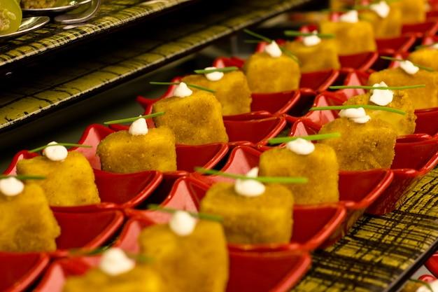 Frango em panado em servir pratos vermelhos, decorado com cebolinha