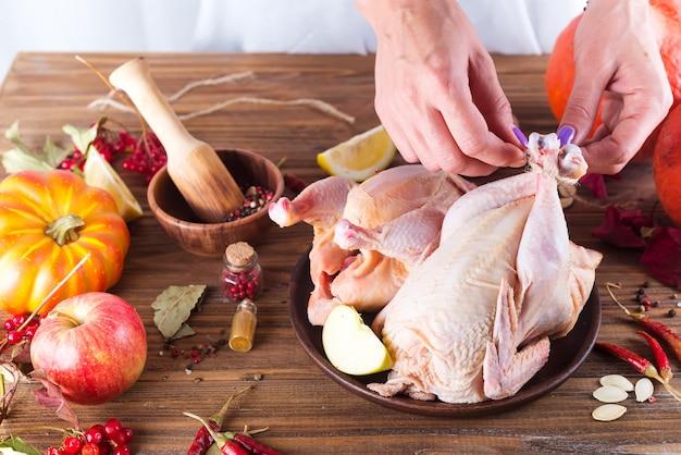 Frango em um prato com maçã de especiarias e laranja em uma mesa de madeira.