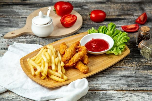 Frango empanado com batatas fritas e ketchup vista lateral