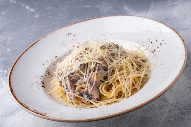 Frango espaguete e cogumelos em um prato.