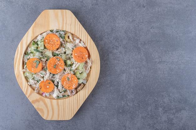 Frango fatiado com cenoura na placa de madeira.