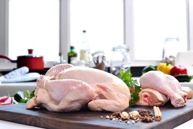 Frango fresco cru com ingredientes para cozinhar em uma tábua de madeira na cozinha