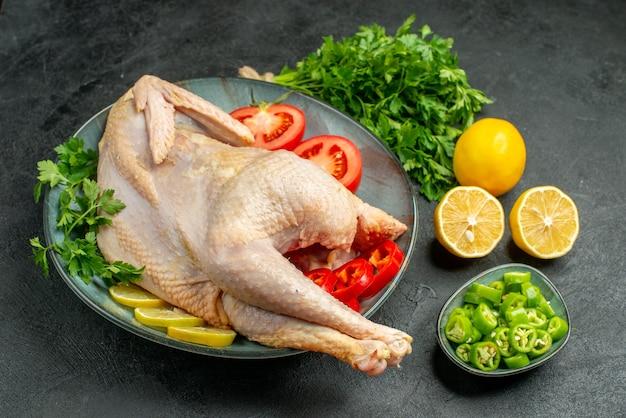 Frango fresco cru de vista frontal dentro do prato com verduras e vegetais em fundo escuro.