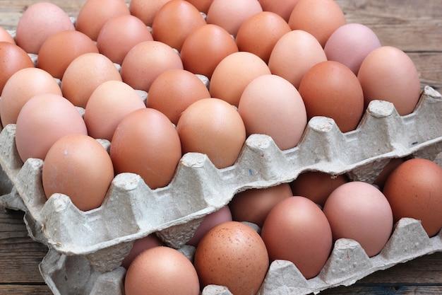 Frango fresco ovos marrons em embalagem em um assoalho de madeira