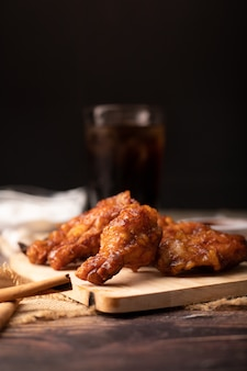 Frango frito churrasco quente e picante coreano na tábua de madeira