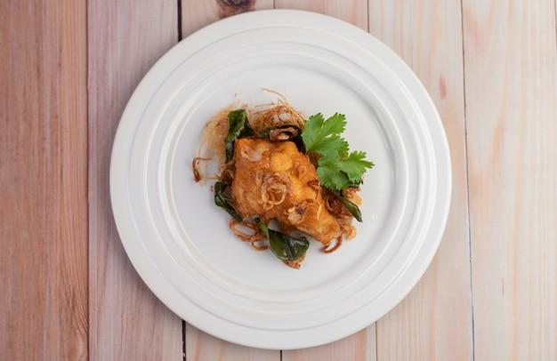 Frango frito com ervas em um prato branco sobre um piso de madeira.