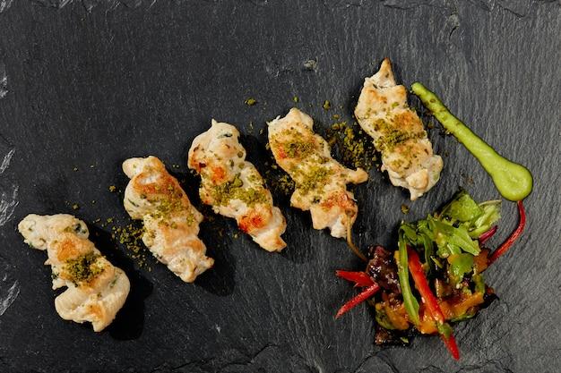 Frango frito com molho coreano no prato preto. Foto Premium