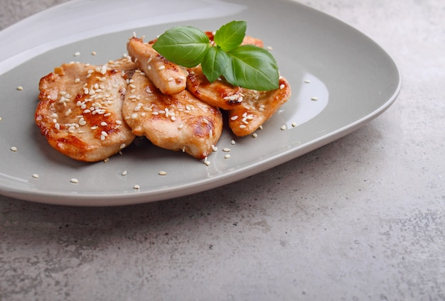 Frango frito com molho de soja em um prato decorado com sementes de gergelim e manjericão, cópia espaço