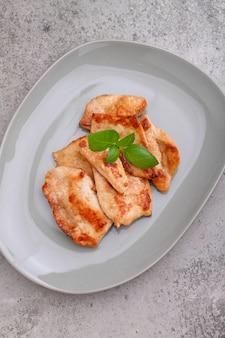 Frango frito com molho de soja em um prato decorado com sementes de gergelim e manjericão, vista superior