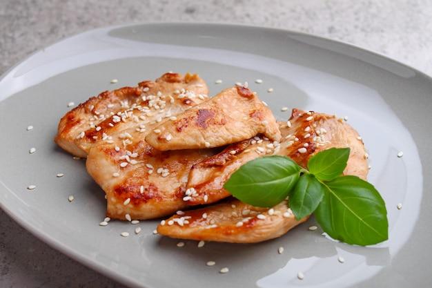 Frango frito com molho de soja em um prato decorado com sementes de gergelim