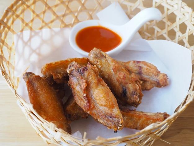 Frango frito com molho na cesta de bambu na mesa de madeira