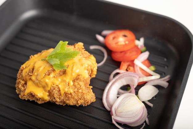 Frango frito com queijo coberto em uma panela preta