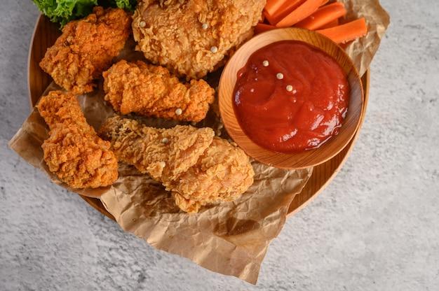 Frango frito crocante em um prato de madeira com molho de tomate e cenoura