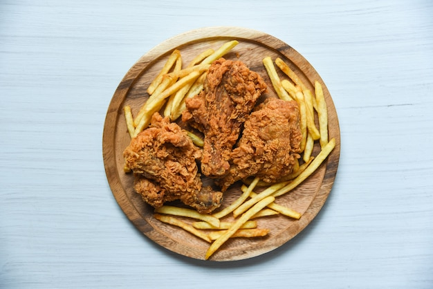 Frango frito crocante na bandeja de madeira com batatas fritas no fundo da mesa de jantar