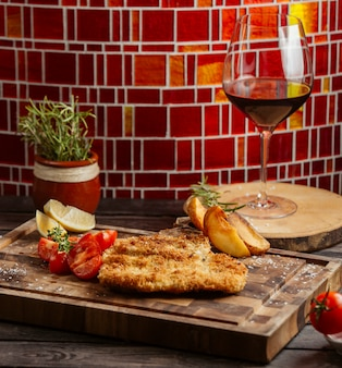 Frango frito crocante servido com tomate e batatas fritas na placa de madeira
