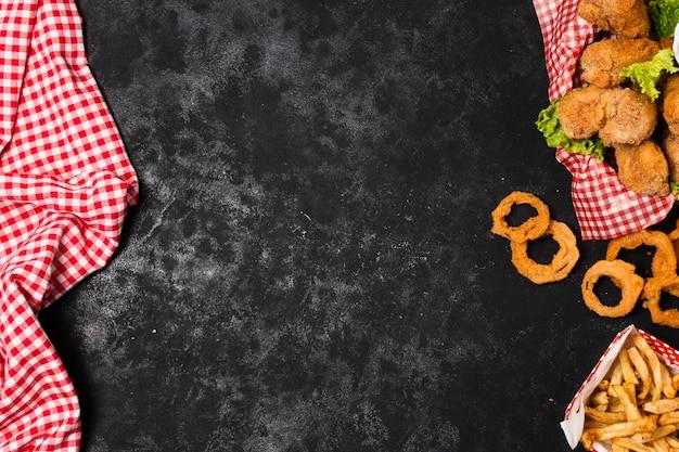 Frango frito e anéis de cebola com espaço de cópia