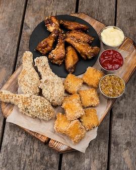 Frango frito em ângulo alto com nuggets e três molhos